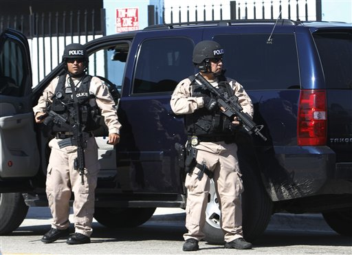 **CORRECTS BYLINE** Police officers is stand near the location of a shootout that erupted in a Miami neighborhood on Thursday, Jan. 20, 2011, killing two Miami-Dade police officers and a suspect, authorities said. Miami-Dade Mayor Carlos Alvarez said the first officer had been shot once and died at the scene. The second officer, who was shot several times, was taken to a hospital and later died, Alvarez said. (AP Photo/Alan Diaz)