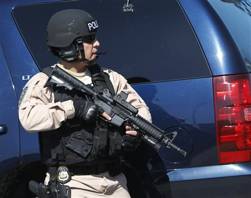 **CORRECTS BYLINE** A heavily-armed police officer is shown near the location of a shootout that erupted in a Miami neighborhood on Thursday, Jan. 20, 2011, killing two Miami-Dade police officers and a suspect, authorities said. Miami-Dade Mayor Carlos Alvarez said the first officer had been shot once and died at the scene. The second officer, who was shot several times, was taken to a hospital and later died, Alvarez said. (AP Photo/Alan Diaz)