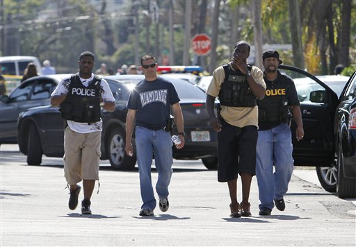 **CORRECTS BYLINE** Police officers are shown near the location of a shootout that erupted in a Miami neighborhood on Thursday, Jan. 20, 2011, killing two Miami-Dade police officers and a suspect, authorities said. Miami-Dade Mayor Carlos Alvarez said the first officer had been shot once and died at the scene. The second officer, who was shot several times, was taken to a hospital and later died, Alvarez said. (AP Photo/Alan Diaz)