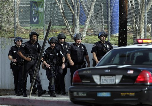 A group of police officers search outside El Camino Real High School in the Woodland Hills section of Los Angeles, Wednesday, Jan. 19, 2011. A school police officer was shot near the high school but his bulletproof vest took the hit Wednesday, one day after an accidental shooting wounded two students at a school on the other side of the city, authorities said. (AP Photo/Jae C. Hong)