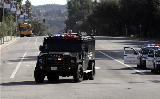 A police vehicle drives past El Camino Real High School in the Woodland Hills section of Los Angeles, Wednesday, Jan. 19, 2011. A school police officer was shot near the high school but his bulletproof vest took the hit Wednesday, one day after an accidental shooting wounded two students at a school on the other side of the city, authorities said. (AP Photo/Jae C. Hong)