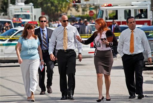 Miami-Dade Mayor Carlos Alvarez, third from left, walks with Miami-Dade Police spokeswoman Cmdr. Nancy Perez, second from right, as they prepare to speak to the media near where a shootout erupted in a Miami neighborhood, killing two Miami-Dade police officers and a suspect, Thursday, Jan. 20, 2011. Alvarez said the first officer had been shot once and died at the scene. The second officer, who was shot several times, was taken to a hospital and later died. (AP Photo/Wilfredo Lee)