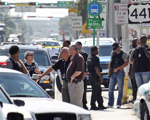 Police officers are shown near the location of a shootout that erupted in a Miami neighborhood on Thursday, Jan. 20, 2011, killing two Miami-Dade police officers and a suspect, authorities said. Miami-Dade Mayor Carlos Alvarez said the first officer had been shot once and died at the scene. The second officer, who was shot several times, was taken to a hospital and later died, Alvarez said. (AP Photo/Wilfredo Lee)