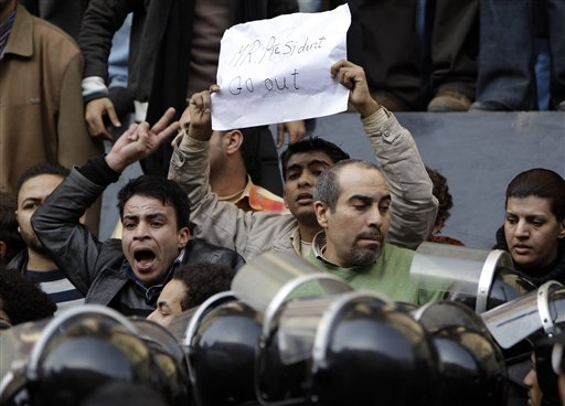 A man holds up a placard reading 'Mr. President go out' as angry Egyptian activist shouts at anti-riot policemen in front of the journalists syndicate in downtown Cairo, Egypt, Wednesday, Jan. 26, 2011. A small gathering of Egyptian anti-government activists tried to stage a second day of protests in Cairo Wednesday in defiance of a ban on any gatherings, but police quickly moved in and used force to disperse the group. (AP Photo/Ben Curtis)