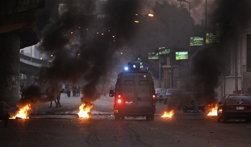 A riot van drives through a burning barricade as Egyptian riot police clash with anti-government activists in downtown Cairo, Egypt, Wednesday, Jan. 26, 2011. Egyptian anti-government activists clashed with police for a second day Wednesday in defiance of an official ban on any protests but beefed up police forces on the streets quickly moved in and used tear gas and beatings to disperse demonstrations. (AP Photo/Ben Curtis)
