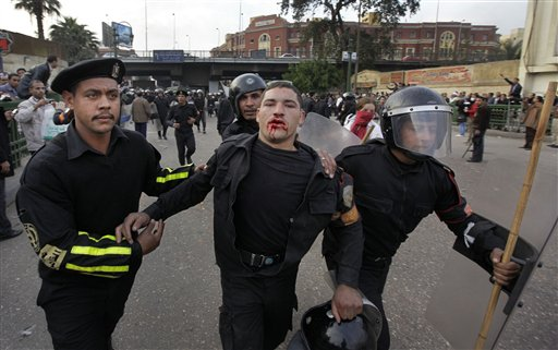 A wounded riot policeman is led away by colleagues as Egyptian riot police clash with anti-government activists in downtown Cairo, Egypt, Wednesday, Jan. 26, 2011. Egyptian anti-government activists clashed with police for a second day Wednesday in defiance of an official ban on any protests but beefed up police forces on the streets quickly moved in and used tear gas and beatings to disperse demonstrations. (AP Photo/Ben Curtis)