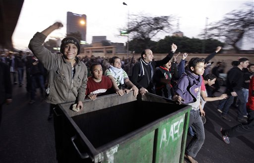 Anti-government activists wheel a rubbish bin to form a barricade as they clash with Egyptian riot police in downtown Cairo, Egypt, Wednesday, Jan. 26, 2011. Egyptian anti-government activists clashed with police for a second day Wednesday in defiance of an official ban on any protests but beefed up police forces on the streets quickly moved in and used tear gas and beatings to disperse demonstrations. (AP Photo/Ben Curtis)