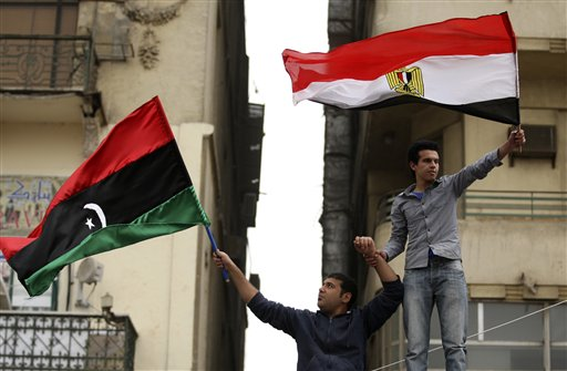 Egyptian protesters a wave Libya's old national flag and an Egyptian flag during the Friday demonstration in the Tahrir Square in Cairo, Egypt, Friday, Feb.25, 2011.The deputy to Osama bin Laden issued al-Qaida's second message since the Egyptian uprising, accusing the nation's Christian leadership of inciting interfaith tensions and denying that the terror network was behind last month's bombing of a Coptic church in Alexandria that killed 21 and sparked protests. (AP Photo/Khalil Hamra)