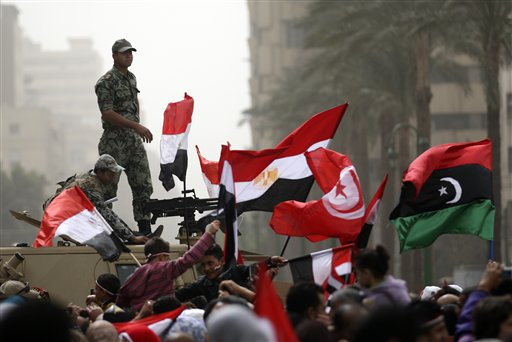 Egyptian army officers guard on top of an armored vehicle as demonstrators wave the Egyptian, Tunisian and Libya's old national flags in the Tahrir Square in Cairo, Egypt, Friday, Feb.25, 2011.The deputy to Osama bin Laden issued al-Qaida's second message since the Egyptian uprising, accusing the nation's Christian leadership of inciting interfaith tensions and denying that the terror network was behind last month's bombing of a Coptic church in Alexandria that killed 21 and sparked protests. (AP Photo/Khalil Hamra)