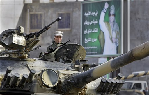 A Libyan army soldier loyal to Libyan Leader Moammar Gadhafi, poster in background, sits in a tank, in Qasr Banashir, southeast of the capital Tripoli, in Libya, Tuesday, March 1, 2011. Government opponents in rebel-held Zawiya repelled an attempt by forces loyal to Moammar Gadhafi to retake the city closest to the capital in six hours of fighting overnight, witnesses said Tuesday. (AP Photo/Ben Curtis)