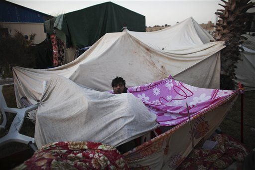 Bangladeshi workers who have been trying to leave Libya for over six days wake up in the morning in a makeshift tent as they wait to be evacuated in the eastern city of Benghazi, Libya, on Tuesday, March 1, 2011. (AP Photo/Tara Todras-Whitehill)