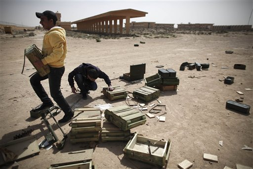 Libyan volunteers take ammunition from inside an army base to be used for the defense against any further Libyan air force raids in the eastern town of Ajdabiya, Libya, on Tuesday March 1, 2011. The U.N. Security Council have imposed an arms embargo on Gadhafi, four of his sons and a daughter and leaders of revolutionary committees accused of much of the violence against opponents, urged an international freeze on Libyan assets and authorized an investigation into Ghadafi's regime for possible crimes against humanity. (AP Photo/Tara Todras-Whitehill)