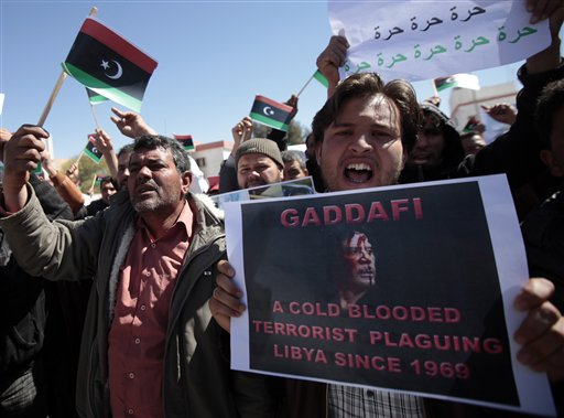 Libyan anti-government protesters, some carrying monarchist-era flags, chant slogans as they demonstrate against Libyan leader Moammar Gadhafi, in the southwestern town of Nalut, Libya, Tuesday, March 1, 2011. The town is currently in control of the Libyan anti-government forces. (AP Photo/Lefteris Pitarakis)