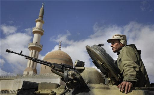 A pro-Gadhafi Libyan soldier sits in an armoured vehicle next to a mosque in Qasr Banashir, southeast of the capital Tripoli, in Libya, Tuesday, March 1, 2011. Government opponents in rebel-held Zawiya repelled an attempt by forces loyal to Moammar Gadhafi to retake the city closest to the capital in six hours of fighting overnight, witnesses said Tuesday. (AP Photo/Ben Curtis)