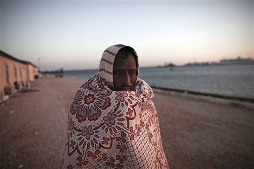 A Bangladeshi worker who has been trying to leave Libya for over six days, walks near the water as he waits at the port in the eastern city of Benghazi, Libya, on Tuesday, March 1, 2011. (AP Photo/Tara Todras-Whitehill)