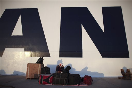 Syrians sit next to the hull of a Greek ship as they wait to be evacuated at the port in the eastern city of Benghazi, Libya, on Tuesday, March 1, 2011. (AP Photo/Tara Todras-Whitehill)
