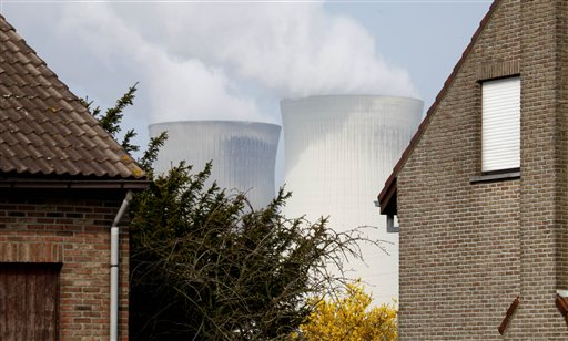 Two nuclear cooling towers are seen between two houses in Doel, Belgium on Tuesday, March 15, 2011. In response to events taking place in Japan, the Belgian government has opened a website with information on evacuation in the event of a nuclear accident and also said that they will make iodine tablets available to all residents in the evacuation zone. Belgium currently has two operating nuclear power plants. (AP Photo/Virginia Mayo)
