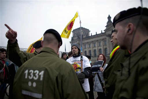 German police officers advise anti nuclear protestors to leave their place in front of Reichtag building, which hosts the German parliament, in Berlin on Tuesday, March 15, 2011. German Chancellor Angela Merkel faces strong protests against her nuclear policy after Japanese nuclear power plants were damaged by Friday's earthquake. (AP Photo/Markus Schreiber)