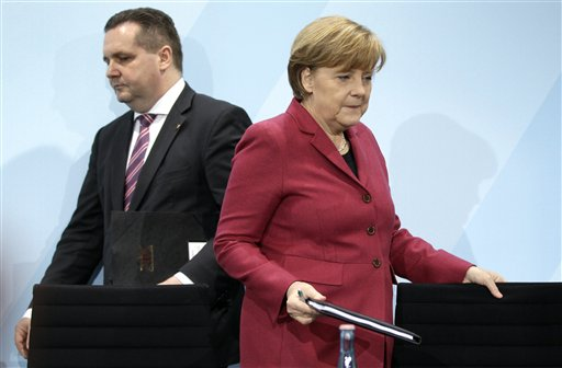 German Chancellor Angela Merkel, right, and the governor of the German state of Baden-Wuerttemberg, Stefan Mappus, left, arrive for a news conference in Berlin, Germany, Tuesday, March 15, 2011. Germany will take seven of its 17 nuclear reactors offline for three months while the country reconsiders plans to extend the life of its atomic power plants in the wake of events in Japan, Chancellor Angela Merkel said Tuesday. (AP Photo/Michael Sohn)