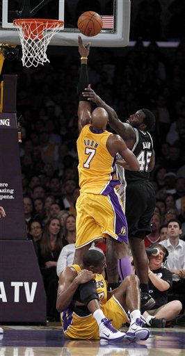 Los Angeles Lakers' Andrew Bynum holds his knee on the floor after being hurt as teammate Lamar Odom and San Antonio Spurs' DeJuan Blair reach for a rebound during the first half of an NBA basketball game in Los Angeles, Tuesday, April 12, 2011. (AP Photo/Chris Carlson)