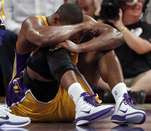 Los Angeles Lakers' Andrew Bynum holds his knee on the floor after being hurt during the first half of an NBA basketball game against the San Antonio Spurs in Los Angeles, Tuesday, April 12, 2011. Bynum hyperextended his right knee. (AP Photo/Chris Carlson)