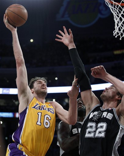 Los Angeles Lakers' Pau Gasol, left, shoots over San Antonio Spurs' Tiago Splitter during the first half of an NBA basketball game in Los Angeles, Tuesday, April 12, 2011. (AP Photo/Chris Carlson)