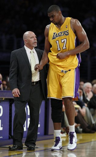 Los Angeles Lakers' Andrew Bynum is helped off the floor by trainer Gary Vitti after injuring his right knee during the second quarter of an NBA basketball game against the San Antonio Spurs in Los Angeles, Tuesday, April 12, 2011. (AP Photo/Chris Carlson)