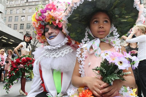 Dinah King, 6, of the Queens borough of New York, foreground right, and a man calling himself Muffinhead, foreground left, pose for photographers as they take part in the Easter Parade along New York's Fifth Avenue Sunday April 24, 2011. (AP Photo/Tina Fineberg)