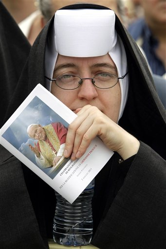 A nun holds a leaflet as she follows a thanksgiving Mass in St. Peter's Square at the Vatican, Monday, May 2, 2011. Tens of thousands of Catholic faithful have filled St. Peter's Square for a Mass of thanksgiving for the beatification of John Paul II. The Mass is being celebrated by the Vatican No. 2, Cardinal Tarcisio Bertone. Among the large crowds entering the square Monday were many Poles overjoyed at Sunday's beatification of the Polish-born pontiff. After Sunday's beatification, about 250,000 faithful filed past John Paul's simple wooden coffin in St. Peter's Basilica. The pope had been buried in the grottoes underneath the church, but his closed casket was brought to the church's center aisle ahead of the beatification. (AP Photo/Pier Paolo Cito)
