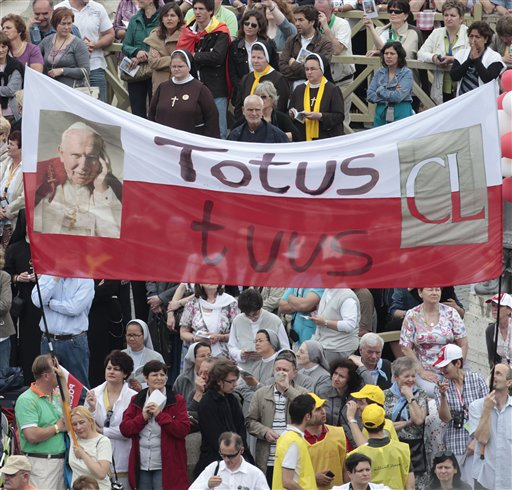 Faithful hold a banner reading in latin Totus tuus (Totally yours) during a thanksgiving Mass in St. Peter's Square at the Vatican, Monday, May 2, 2011. Tens of thousands of Catholic faithful have filled St. Peter's Square for a Mass of thanksgiving for the beatification of John Paul II. The Mass is being celebrated by the Vatican No. 2, Cardinal Tarcisio Bertone. Among the large crowds entering the square Monday were many Poles overjoyed at Sunday's beatification of the Polish-born pontiff. After Sunday's beatification, about 250,000 faithful filed past John Paul's simple wooden coffin in St. Peter's Basilica. The pope had been buried in the grottoes underneath the church, but his closed casket was brought to the church's center aisle ahead of the beatification. (AP Photo/Gregorio Borgia)