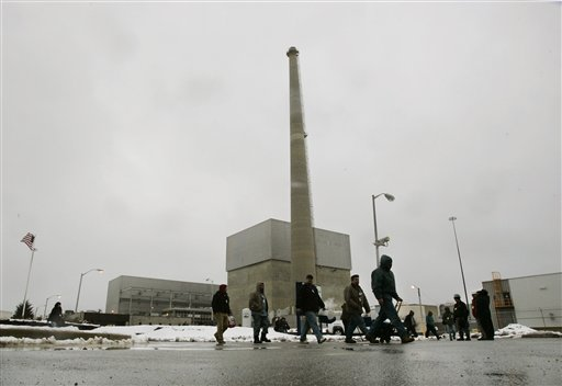 In this Thursday, Feb. 25, 2010 picture, workers walk in front of a large square building that houses the nuclear reactor at the Oyster Creek nuclear plant in Lacey Township, N.J. Called 'Oyster Creak' by some critics because of its aging problems, this boiling water reactor began running in 1969 and ranks as the country's oldest operating commercial nuclear power plant. Its license was extended in 2009 until 2029, though utility officials announced in December 2010 that they'll shut the reactor 10 years earlier, rather than build state-ordered cooling towers. (AP Photo/Mel Evans)