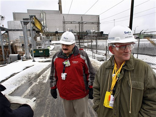 In this Thursday, Feb. 25, 2010 picture, Exelon's Pete Tamburro, left, and David Benson stand outside the Oyster Creek nuclear plant, background, in Lacey Township, N.J. Spokesman Benson said the reactor 'is as safe today as when it was built.' Yet plant officials have been trying to arrest rust on its 100-foot-high, radiation-blocking steel drywell for decades. The problem was declared solved long ago, but a rust patch was found again in late 2008. Benson said the new rust was only the size of a dime, but acknowledged there was 'some indication of water getting in.' (AP Photo/Mel Evans)