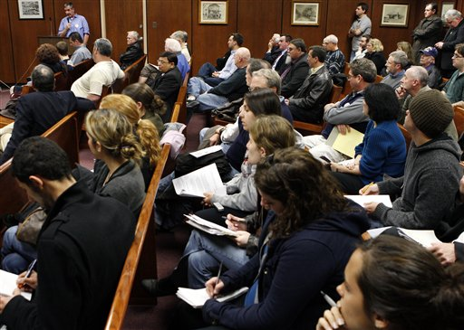 In this Wednesday, Feb. 24, 2010 picture, William de Camp, at podium at background left, speaks in a crowded room in Lacey Township, N.J. during a public hearing on a state proposal to force the Oyster Creek nuclear plant to build cooling towers to protect Barnegat Bay from its hot water discharges. Called 'Oyster Creak' by some critics because of its aging problems, this boiling water reactor began running in 1969 and ranks as the country's oldest operating commercial nuclear power plant. Its license was extended in 2009 until 2029, though utility officials announced in December that they'll shut the reactor 10 years earlier, rather than build state-ordered cooling towers. (AP Photo/Mel Evans)