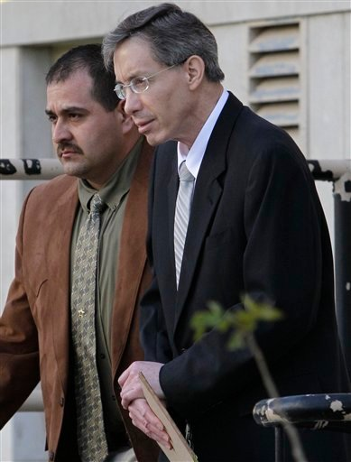 FILE - In this Aug. 5, 2011 file photo, Warren Jeffs, right, is escorted out of the Tom Green County Courthouse by a law enforcement officer in San Angelo, Texas. The polygamist leader has been hospitalized after not eating or drinking enough. (AP Photo/Tony Gutierrez, File)