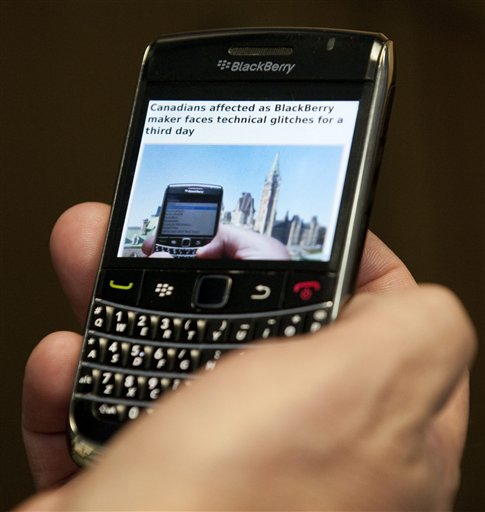 In this photo taken Wednesday, Oct. 12, 2011, a Blackberry subscriber holds a Research in Motion Blackberry in Ottawa. BlackBerry services buzzed back to life across the world Thursday, Oct. 13, after a three-day outage that interrupted email messages and Internet services for millions of customers.(AP Photo/The Canadian Press, Adrian Wyld)
