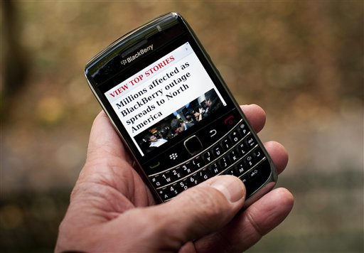 A Blackberry user reads a story about a Blackberry outage that is affecting millions of users of the smartphone that has now spread to North America Wednesday, Oct. 12, 2011, in Montreal. Sporadic outages of BlackBerry messaging and email service spread to the U.S. and Canada on Wednesday, as problems stretched into the third day for Europe, Asia, Latin America and Africa. (AP Photo/The Canadian Press, Paul Chiasson) THE CANADIAN PRESS/Paul Chiasson