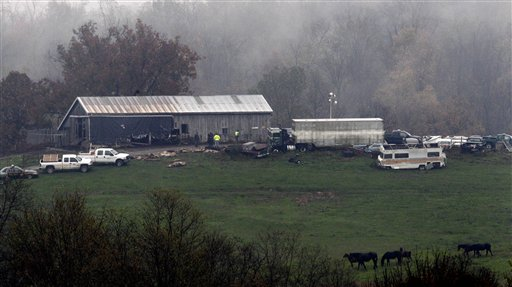 Investigators look around a barn on a wild-animal preserve Wednesday, Oct. 19, 2011, in Zanesville, Ohio. Police with assault rifles stalked a mountain lion, grizzly bear and monkey still on the loose after authorities said their owner apparently freed dozens of wild animals and then killed himself. (AP Photo/Tony Dejak)