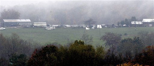 The Muskingum County Animal Farm is shown Wednesday, Oct. 19, 2011, in Zanesville, Ohio. The house is on the right. The barn on the left and cages for other animals are between the house and the barn. Police with assault rifles stalked a mountain lion, grizzly bear and monkey still on the loose after authorities said their owner apparently freed dozens of wild animals and then committed suicide. (AP Photo/Tony Dejak)