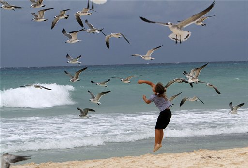 A child plays with seagulls at the beach in Playa del Carmen, Mexico, during the approach of Tropical Storm Rina Thursday Oct. 27, 2011. Rina was downgraded from a hurricane to a tropical storm Thursday afternoon after many tourists had already cut short their trips to Cancun and other Caribbean resorts ahead of what once threatened to be a Category 3 storm. (AP Photo/Marco Ugarte)