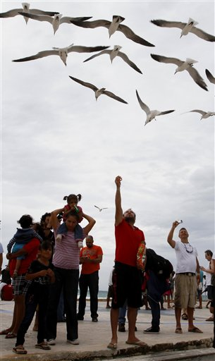 Tourists feed seagulls on the pier during the approach of Tropical Storm Rina in Playa del Carmen, Mexico, Thursday Oct. 27, 2011. Rina was downgraded from a hurricane to a tropical storm Thursday afternoon after many tourists had already cut short their trips to Cancun and other Caribbean resorts ahead of what once threatened to be a Category 3 storm. (AP Photo/Marco Ugarte)
