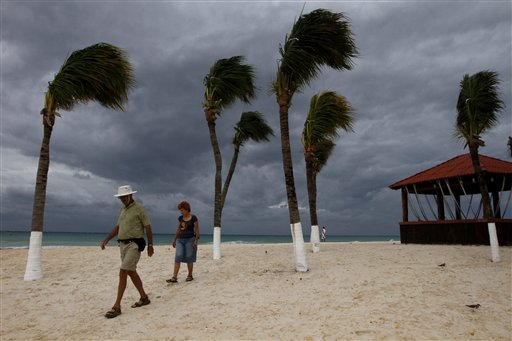 Tourists walk on the beach during the approach of Tropical Storm Rina on Playa del Carmen, Mexico, Thursday Oct. 27, 2011. Rina was downgraded from a hurricane to a tropical storm after it threatened to be a Category 3 storm. (AP Photo/Marco Ugarte)