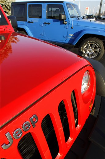This photo taken Sunday, Dec. 11, 2011, shows 2012 Chrysler Jeep Wranglers for sale at a auto dealership in Springfield, Ill. The company ended the year with a 37 percent increase in December sales on strong demand for the Jeep Wrangler and Chrysler 200 sedan. (AP Photo/Seth Perlman)