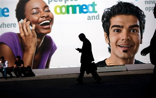 A visitor uses his mobile phone as he walks past a big banner announcing new mobiles at the world's largest mobile phone trade show in Barcelona, Spain, Thursday, March 1, 2012. (AP Photo/Emilio Morenatti)