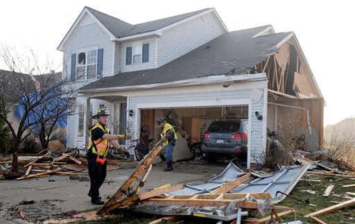 Firemen help clear debris from a yard on Noble Street in the Huron Farms area, Friday, March 16, 2012, after a tornado hit Dexter, Mich., Thursday evening. (AP Photo/AnnAbor.Com, Angela J. Cesere)