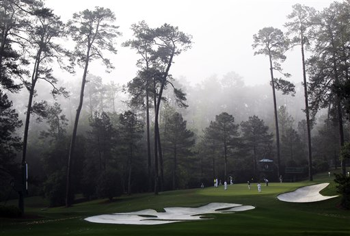 Players putt on the 10th green in the morning fog during a practice round for the Masters golf tournament Wednesday, April 4, 2012, in Augusta, Ga. (AP Photo/Chris O'Meara)