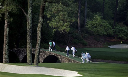 Tiger Woods, left, walks across the Ben Hogan Bridge on the 12th hole with Sean O'Hair, right and Mark O'Meara during a practice round for the Masters golf tournament Wednesday, April 4, 2012, in Augusta, Ga. (AP Photo/Chris O'Meara)