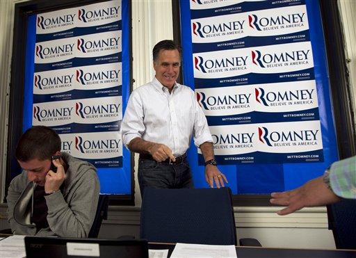 Republican presidential candidate, former Massachusetts Gov. Mitt Romney, center, points to his chair before working the phones at a call center at his Pennsylvania campaign headquarters in Harrisburg, Pa., Thursday, April 5, 2012. Campaign volunteer Jordan Furr of Mechanicsburg, Pa. is at left. (AP Photo/Steven Senne)